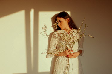 Felicia Simion BRUNETTE WOMAN HOLDING BLOSSOM IN SUNLIGHT Women