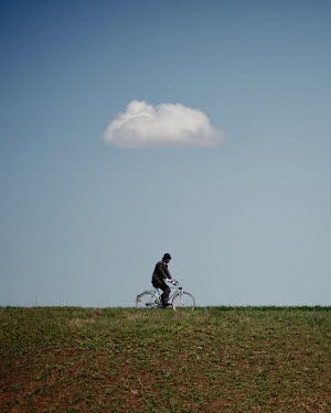 Felicia Simion MAN IN HAT CYCLING IN FIELD WITH CLOUD Men