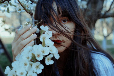 Felicia Simion BRUNETTE WOMAN HOLDING BRANCH OF BLOSSOM OUTDOORS Women