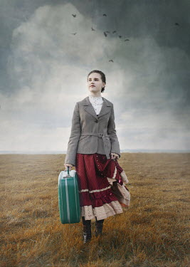 Anna Buczek GIRL CARRYING SUITCASE IN STORMY COUNTRYSIDE Children
