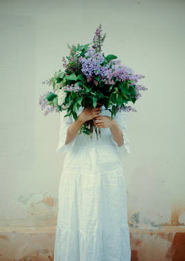 Felicia Simion WOMAN HOLDING BUNCH OF FLOWERS ON FRONT OF FACE Women