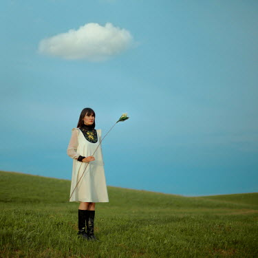 Felicia Simion GIRL HOLDING FLOWER IN FIELD WITH BLUE SKY Women