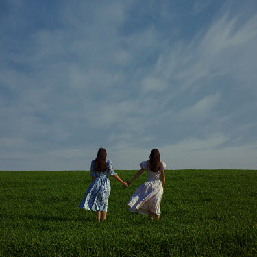 Felicia Simion TWO WOMEN HOLDING HANDS IN FIELD WITH BLUE SKY Women