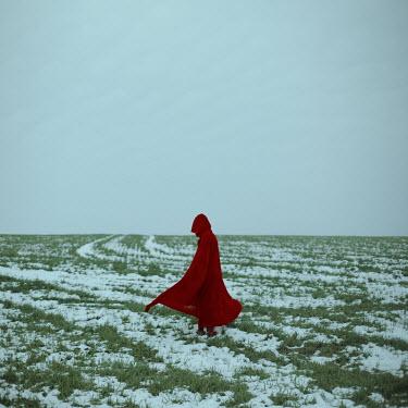 Felicia Simion WOMAN IN HOODED CAPE IN SNOWY LANDSCAPE Women
