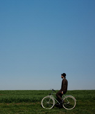 Felicia Simion MAN IN HAT ON BICYCLE IN FIELD WITH BUE SKY Men