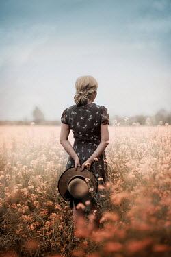 Ildiko Neer Blonde hair woman holding hat in flower field