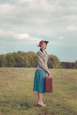 Joanna Czogala RETO WOMAN CARRYING SUITCASE IN COUNTRYSIDE Women
