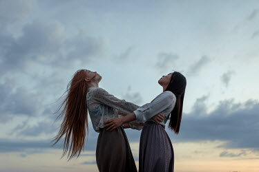 Ulyana Naydenkova TWO GIRLS EMBRACING OUTDOORS WITH SUNSET Women