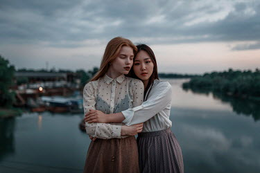 Ulyana Naydenkova TWO GIRLS HUGGING BY RIVER AT DUSK Women