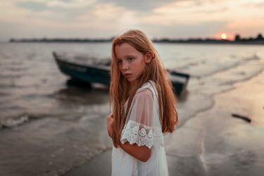 Ulyana Naydenkova LITTLE GIRL WITH RED HAIR STANDING ON BEACH AT SUNSET Children