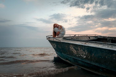 Ulyana Naydenkova GIRL HUDDLED ON WEATHERED BOAT BY SEA Children