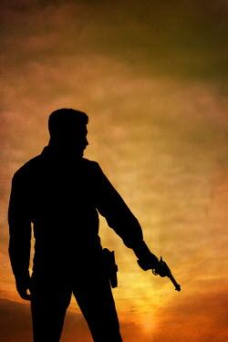 Magdalena Russocka silhouette of man holding revolver at sunset