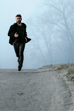 Magdalena Russocka modern man running on empty road in woods
