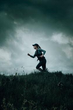 Rekha Garton WOMAN WITH GUN RUNNING IN FIELD Women