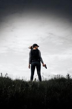 Rekha Garton WOMAN WITH GUN STANDING IN FIELD Women
