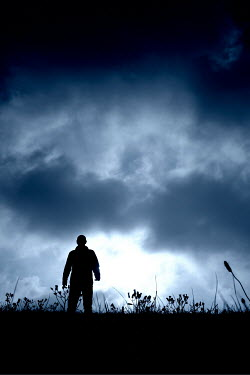 Tim Robinson SILHOUETTED MAN STANDING IN FIELD AT DUSK Men