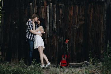 Alina Zhidovinova TEENAGE COUPLE EMBRACING BY FENCE WITH GUITAR Couples