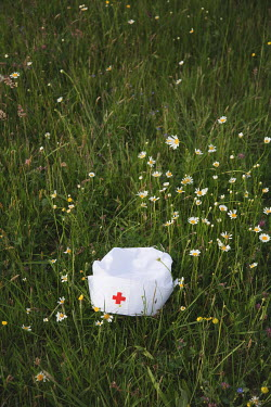 Joanna Czogala NURSE'S CAP WITH RED CROSS LYING ON GRASS Miscellaneous Objects