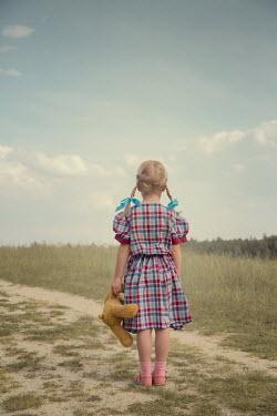 Joanna Czogala LITTLE GIRL HOLDING TEDDY ON SUITCASE OUTDOORS Children