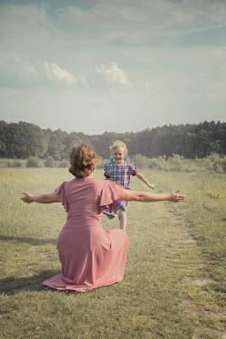 Joanna Czogala DAUGHTER RUNNING TO MOTHER IN SUMMERY COUNTRYSIDE Children