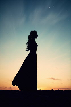 Magdalena Russocka SILHOUETTED WOMAN STANDING OUTDOORS AT SUNSET Women