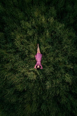 Rekha Garton WOMAN IN PINK LYING IN FIELD FROM ABOVE Women