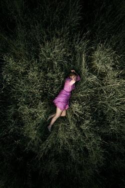 Rekha Garton WOMAN LYING IN FIELD POINTING UP AT CAMERA Women