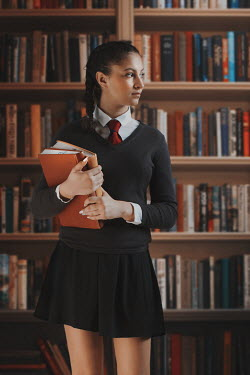 Robin Macmillan TEENAGE SCHOOLGIRL HOLDING BOOKS IN LIBRARY Children