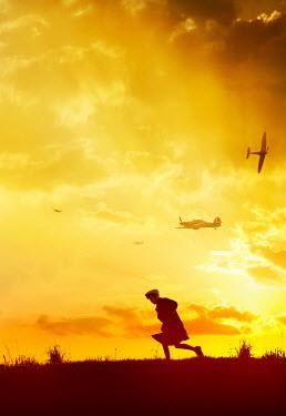 Stephen Mulcahey BOY RUNNING AT SUNSET WITH WAR PLANES Children