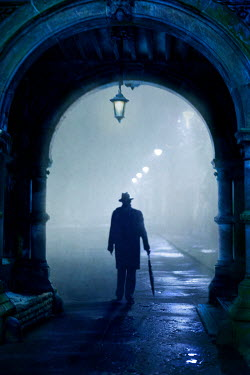 Lee Avison mysterious man in overcoat and fedora walking through an archway at night