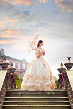 Lee Avison beautiful victorian woman standing on stone steps in the grounds of a mansion house