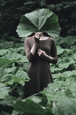 Alina Zhidovinova WOMAN IN GARDEN COVERING FACE WITH LARGE LEAF Women