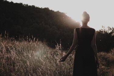 Alina Zhidovinova WOMAN STANDING IN SUNLIT COUNTRYSIDE AT DUSK Women