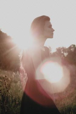 Alina Zhidovinova SERIOUS WOMAN STANDING IN SUNLIT COUNTRYSIDE Women