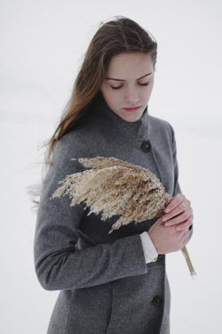 Alina Zhidovinova GIRL HOLDING GRASS OUTDOORS IN WINTER Women