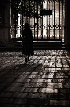 Nikaa WOMAN WALKING BY ORNATE GATE IN SHADOW Women