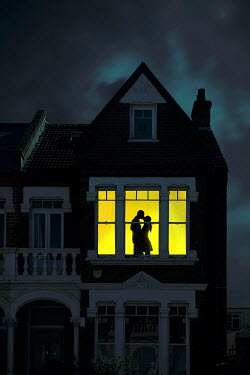 Miguel Sobreira SILHOUETTED COUPLE KISSING BY WINDOW AT NIGHT Couples