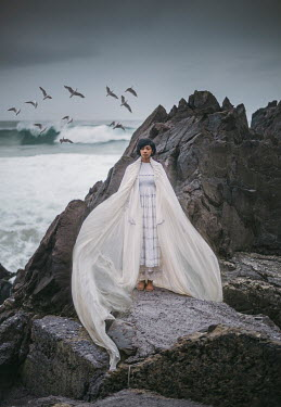Eve North Young Indian woman in white cape by on rocks by sea