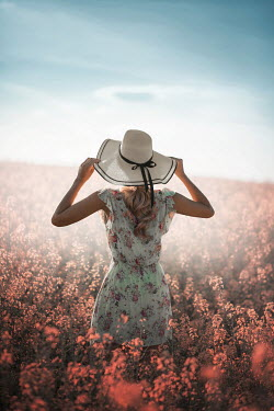 Ildiko Neer Young woman with sun hat in meadow