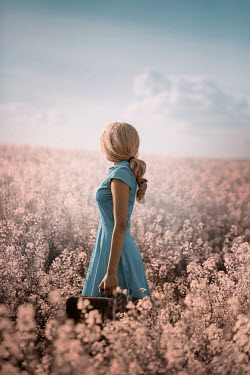 Ildiko Neer Young woman in blue dress carrying suitcase in meadow