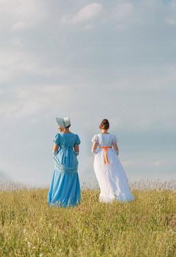Joanna Czogala Young women in Victorian dresses standing in field