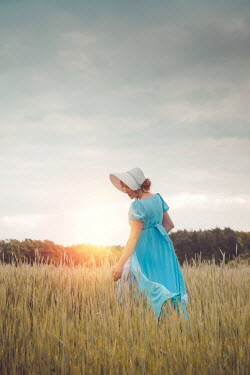 Joanna Czogala Young woman in blue dress and bonnet in field at sunset