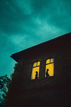 Joanna Czogala Couple standing back to back in windows of house at night