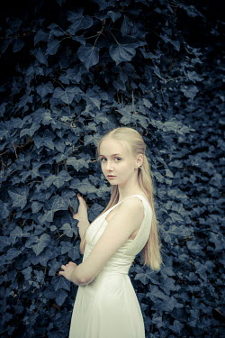 Nic Skerten Young woman in white dress by vines