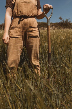 Shelley Richmond Young woman with overalls holding shovel in field