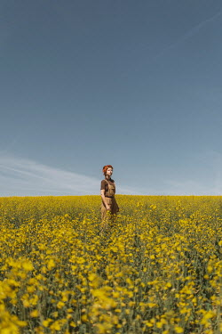 Shelley Richmond Young woman in overalls standing in meadow