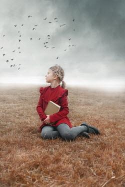 Anna Buczek BLONDE LITTLE GIRL SITTING IN FIELD WITH BOOK Children