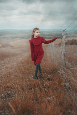 Anna Buczek SAD LITTLE GIRL HOLDING FENCE IN COUNTRYSIDE Children