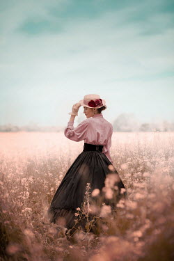 Ildiko Neer Victorian woman holding hat in flower field