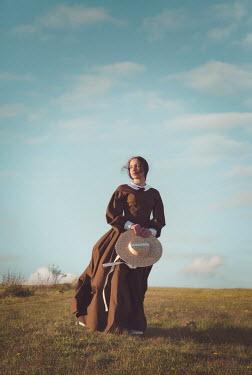 Joanna Czogala HISTORICAL WOMAN HOLDING HAT IN WINDY COUNTRYSIDE Women